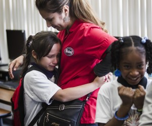 Daisy Ambriz, hugs her daughter Brienna Morales, 8, after The Rogers Foundation awarded scholarships for students Wednesday, January 21, 2015 at Reynaldo Martinez Elementary School, 350 East Judson Avenue, North Las Vegas. On the right is Damya Sanders, 8,also a recipient of a scholarship. The non-profit organization announce the launch of grants and college scholarships for 25 students at the school.(Jeff Scheid/Las Vegas Review-Journal)